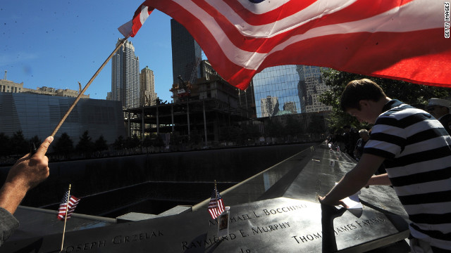 A flag is held over the reflection pool during remembrance ceremonies on Tuesday, September 11, 2012, for the 11th anniversary of the terrorist attacks at the World Trade Center site in New York. The 2001 attacks resulted in the deaths of nearly 3,000 people after hijacked planes crashed into the World Trade Center, the Pentagon in Arlington, Virginia, and a field in Shanksville, Pennsylvania.