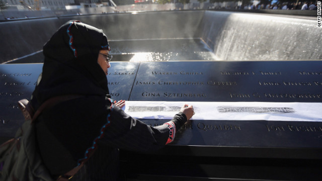 Khudeza Begum etches the name of her slain nephew from the memorial of the 9/11 attacks.