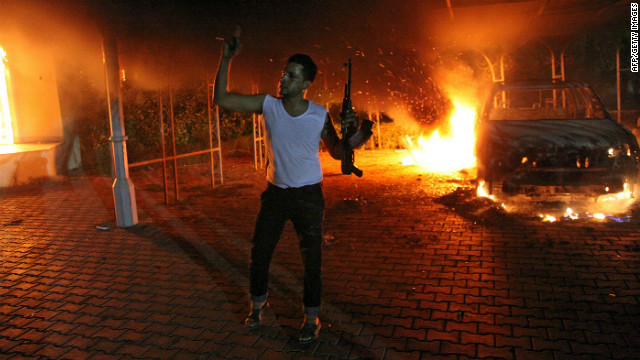 An armed man waves his rifle as buildings and cars are engulfed in flames after being set on fire inside the U.S. Consulate compound in Benghazi, Libya, late on Tuesday, September 11. An armed mob protesting a film they said offended Islam attacked the consulate in Benghazi and set fire to the building, killing one American staff member, witnesses and officials said.