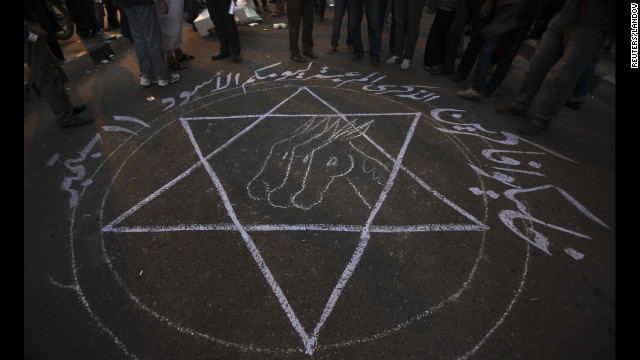People stand around a drawing that says 'Remember your black day 11 September' during the attacks in Cairo.