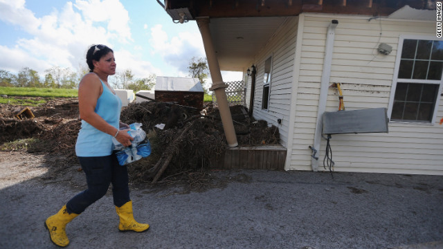 On Friday, September 7, Gina Hunter walks past the front porch of her home, which washed onto a levee in Plaquemines Parish in Braithwaite, Louisiana. &quot;I never expected to have the levee as my backyard,&quot; Hunter says. Louisiana officials estimate at least 13,000 homes were damaged by Hurricane Isaac. 