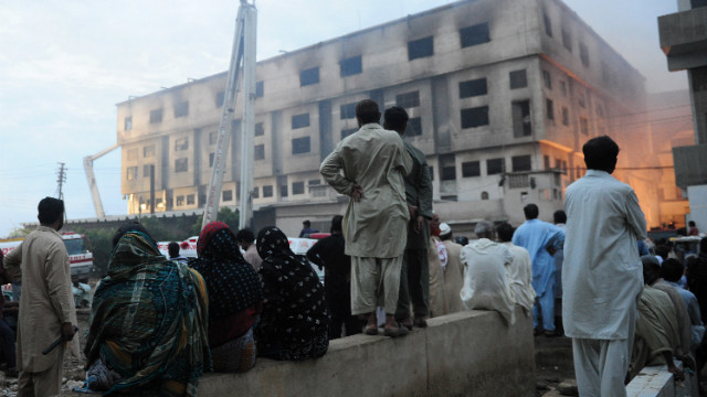 Pakistani residents watch the rescue operation in the garment factory in Karachi. Officials say they don't know the cause of the fire.