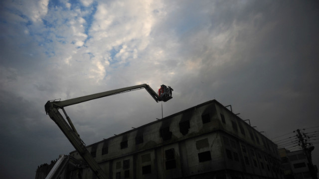 Emergency crews work at the scene of a deadly fire at a garment factory in Karachi, Pakistan, on September 12.