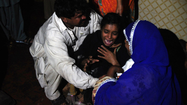 A Pakistani woman mourns the death of relatives in the fire.