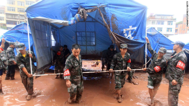 Rescuers move a tent at a temporary hospital destroyed by floodwaters on Tuesday, September 11, in Yiliang County, Yunnan Province, China. Downpours have flooded some settlements for the homeless quake victims and triggered mudslides in the mountainous county. At least 81 people were killed and 821 others injured after two earthquakes jolted the border of Yunnan and Guizhou provinces on Friday.