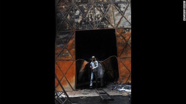 A Pakistani rescue worker leaves the burned out garment factory in Karachi Wednesday, the day after a fire there left at least 258 people dead.