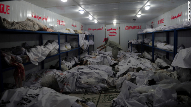 A Pakistani morgue employee identifies the body of a worker who died in a garment factory fire in Karachi onTuesday.
