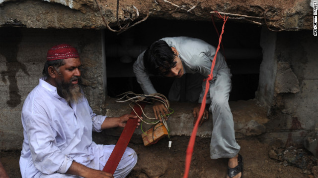 Pakistani men sort through what's left after a factory fire that killed more than 250 people in Karachi.