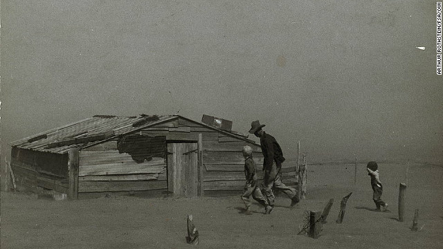 A farmer and sons walk in the face of a dust storm in Cimarron County, Oklahoma, in April 1936.