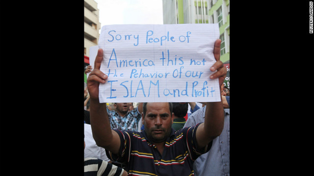 A demonstrator in Benghazi, Libya, on Wednesday, September 12, holds a message during a rally to condemn the killers of the U.S. ambassador to Libya, Chris Stevens, and three others during the attack on the U.S. Consulate. <a href='http://www.cnn.com/2012/09/11/middleeast/gallery/cairo-embassy/index.html'>Photos: Protesters storm U.S. Embassy buildings</a>