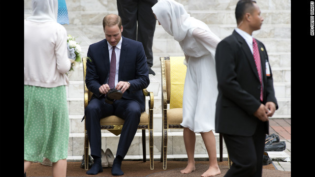 The royal couple put their shoes on after visiting the KLCC Mosque in Kuala Lumpur on Friday.