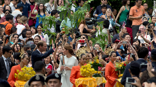 A crowd takes photos of Prince William and Catherine, Duchess of Cambridge, as they walk in the KLCC gardens in Kuala Lumpur on Friday.
