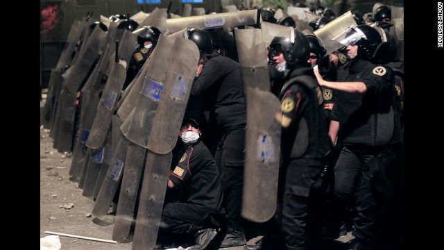 Riot police take cover from stones thrown by protesters on Thursday.