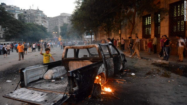 A burned-out pickup sits between Egyptian protesters and riot police in Cairo<br />