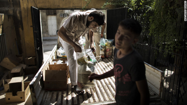 Syrian volunteers distribute food to residents Thursday in Aleppo.