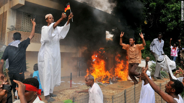 A Sudanese demonstrator burns a German flag after torching the German Embassy in Khartoum on Friday.