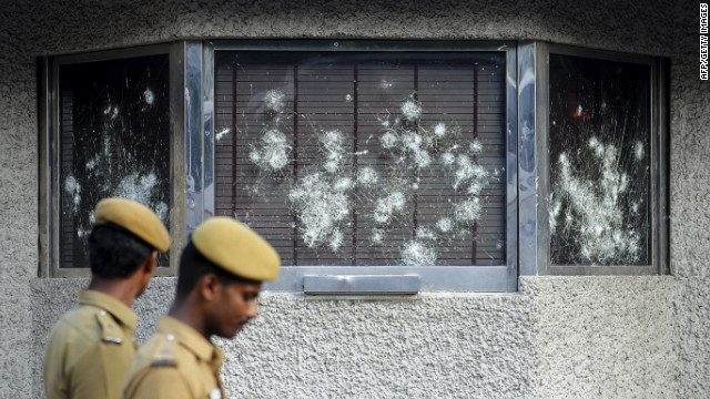 Indian policemen walk past smashed windows of the U.S. Consulate building, caused by a mob of demonstrators protesting against an anti-Islam film, in Chennai, India, on Friday, September 14.
