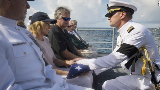 U.S. Navy Capt. Steve Shinego, commanding officer of the USS Philippine Sea, presents the U.S. flag to Carol Armstrong following the burial at sea service.