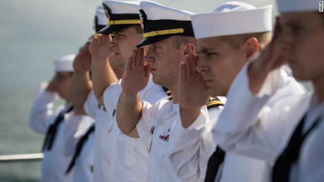 Navy members salute in honor of Armstrong.