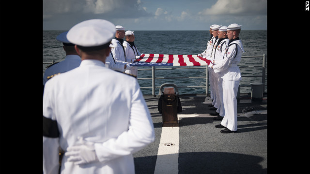 Members of the U.S. Navy ceremonial guard hold an American flag over the Armstrong's remains. 