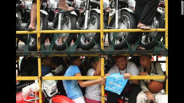 A group of Filipino commuters ride on top of a delivery truck as it maneuvers on a flooded street in Paranaque, south of Manila, on Saturday.