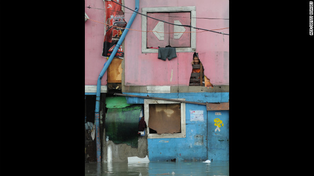 A resident peers through his half-submerged house in Manila.