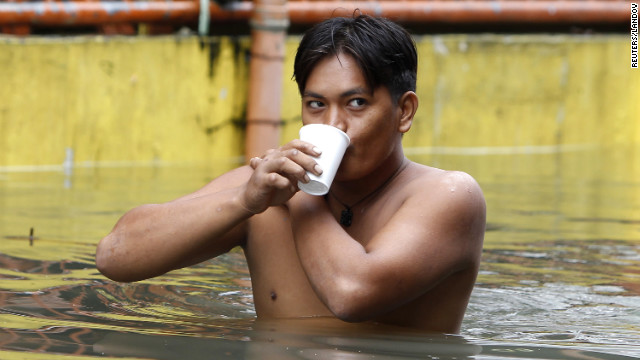 A man drinks a cup of coffee as he wades through water in San Juan on Saturday.