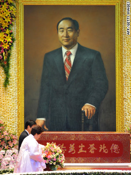 Han Hak Ja (front), wife of late Unification Church founder Sun Myung Moon, mourns during his funeral ceremony at the Cheongshim Peace World Center in Gapyeong, South Korea. More than 30,000 mourners attended the elaborate, flower-strewn funeral.