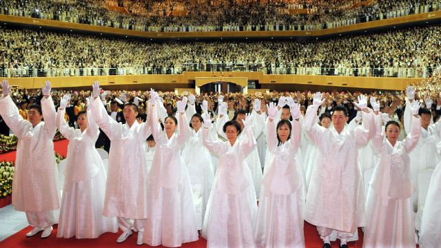 Unification Church followers gesture at the funeral.