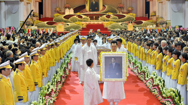 Relatives of Moon carry his portrait during the funeral procession.