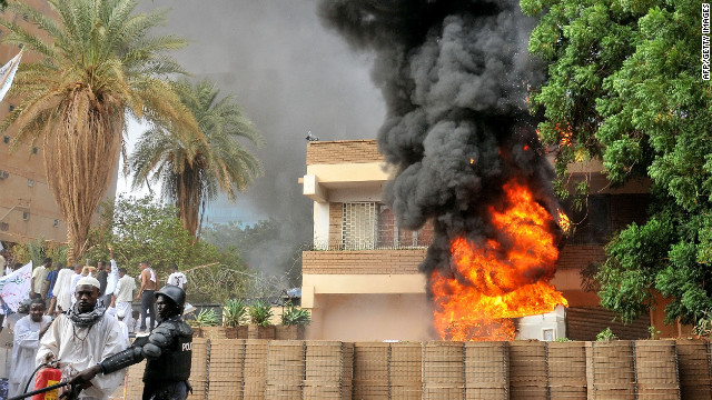 Smoke billows from the burning German Embassy in Khartoum, Sudan, as a policeman stands next to a man preparing to extinguish the fire caused by protesters the anti-Islam film. Around 5,000 protesters in the Sudanese capital stormed the embassies of Britain and Germany, which were torched and badly damaged.