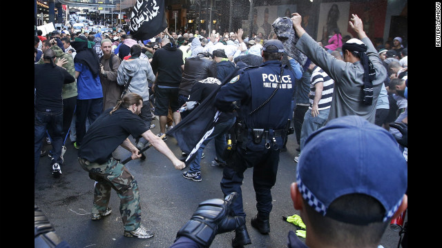 A protester hits a policeman with a pole in Sydney's central business district on Saturday, September 15. Anger over an anti-Islam video, &quot;The Innocence of Muslims,&quot; spread to Australia on Saturday, and protesters took to the streets of the country's capital.