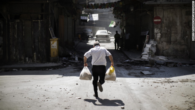 A Syrian man carrying grocery bags tries to dodge sniper fire as he runs through an alley near a checkpoint manned by the Free Syria Army in Aleppo on September 14.