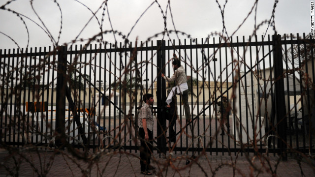 A protester climbs on a gate of the U.S. Consulate in Karachi, Pakistan, on Sunday.