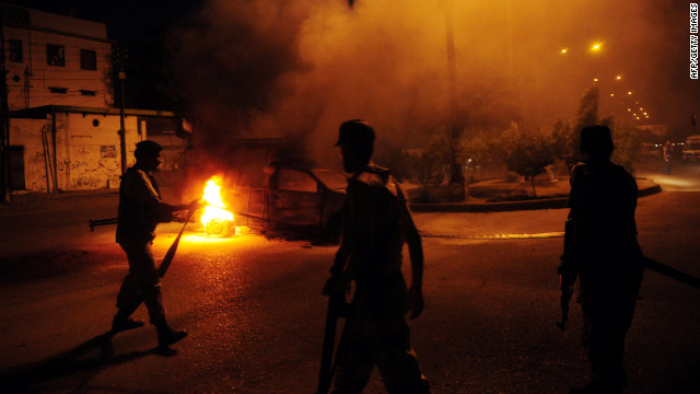 Pakistani paramilitary soldiers stand near a burning police van during an anti-U.S. protest organized by Pakistani Shiite Muslims in Karachi on Sunday.