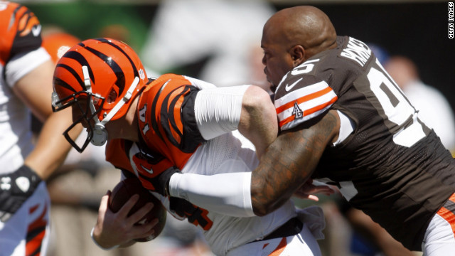 Quarterback Andy Dalton of the Cincinnati Bengals is tackled by Juqua Parker of the Cleveland Browns on Sunday at Paul Brown Stadium in Cincinnati.