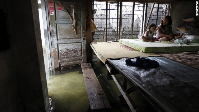 Filipino sisters Maria Fe, left, and Roxanne Jaime sit on an elevated bed inside their flooded home in Malabon City, Philippines, on Sunday.