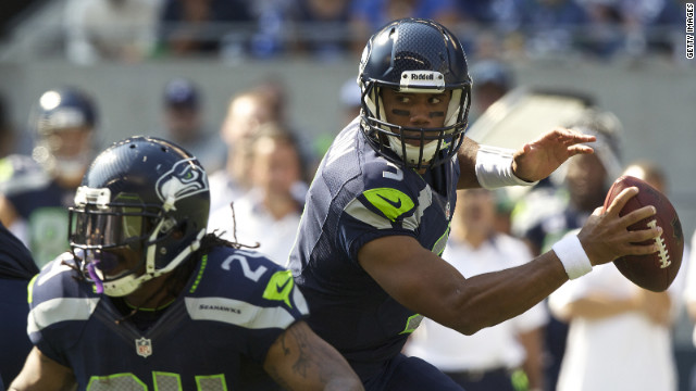 Russell Wilson of the Seattle Seahawks, right, rolls out of the pocket while Marshawn Lynch blocks during Sunday's game against the Dallas Cowboys at CenturyLink Field in Seattle.