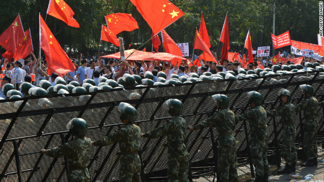 Chinese para-military police create a barrier to prevent protesters from breaching the Japanese embassy in Beijing.