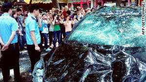 People take pictures of a Japanese car damaged in Xi\'an on Saturday.