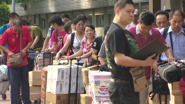 转自CNN,麻烦MCer帮忙翻译一下:Daily stampede of Chinese 'grey traders' angers Hong