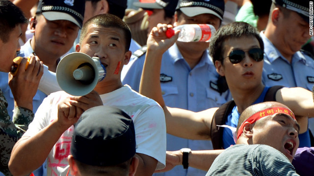 Chinese protesters throw bottles in an anti-Japan rally outside the Japanese embassy on Tuesday in Beijing.
