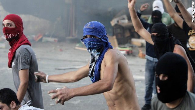 Palestinian protesters throw stones at Israeli security forces during clashes that erupted after a demonstration against an amateur anti-Islam film in Shuafat refugee camp, Jerusalem, on Tuesday. Hundreds of Palestinians protesting against the movie clashed with Israeli border police in East Jerusalem, hurling stones and firebombs at a checkpoint, the military and reporters said.
