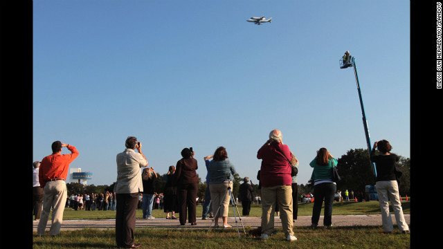 Spectators watch as Endeavour is carried over Stennis Space Center in Hancock County, Mississippi, on Wednesday.