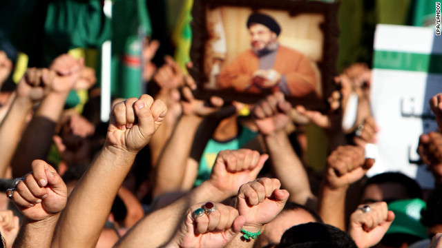 Supporters of Hezbollah hold a picture depicting Hezbollah leader Hassan Nasrallah and chant the slogan