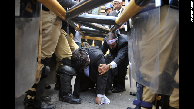 Police try to stop Pakistani lawyers crawling under a barrier as they try to reach the U.S. Embassy in the diplomatic enclave during a protest against an anti-Islam movie in Islamabad on Wednesday. 