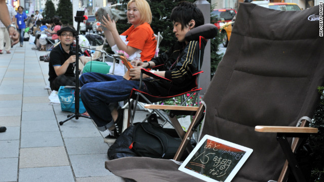 Apple fans line up outside an Apple Store in Tokyo on Thursday. The iPad in the chair reads &quot;15 hours more for iPhone 5.&quot;