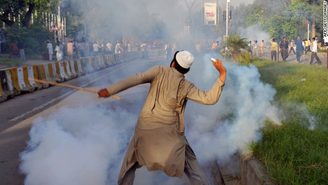 A Pakistani protester throws a tear gas shell back toward police on Thursday.