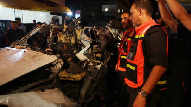 Palestinians gather around the wreckage of a car targeted by an Israeli aircraft in the town of Rafah on September 19, 2012.