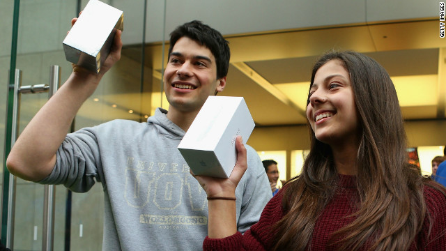 The first customers to purchase their new iPhone 5s exit an Apple flagship store on George street in Syndey, Australia.
